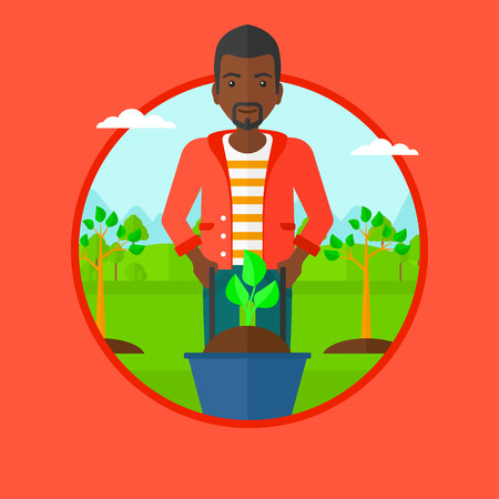 An african man pushing wheelbarrow with plant and dirt in park. Gardener with wheelbarrow on a background of newly planted trees. Vector flat design illustration in the circle isolated on background.