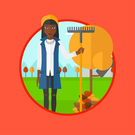 An african woman raking autumn leaves. Woman with rake standing near tree and heap of leaves. Woman tidying leaves in garden. Vector flat design illustration in the circle isolated on background.