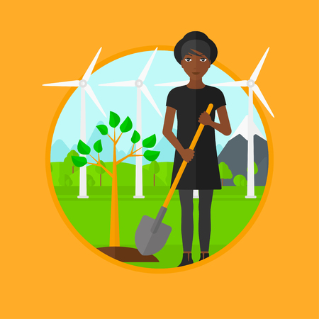 An african-american woman standing with shovel near newly planted tree. Woman planting tree on a background of wind turbines. Vector flat design illustration in the circle isolated on background.
