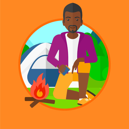 camping site: An african-american man kindling a campfire on the background of camping site with tent. Tourist relaxing near campfire. Vector flat design illustration in the circle isolated on background.