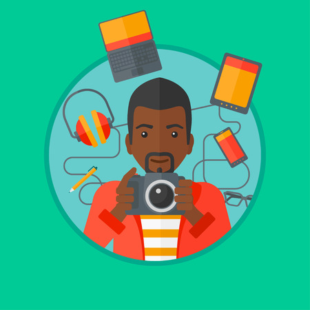An african-american man taking photo with digital camera. Young man surrounded with gadgets. Man using many electronic gadgets. Vector flat design illustration in the circle isolated on background. Illustration