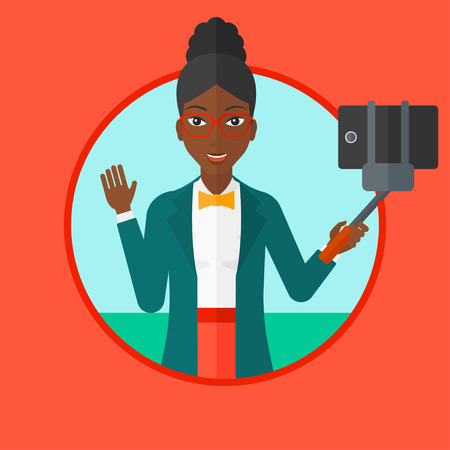 woman cellphone: African-american woman making selfie with a selfie-stick. Woman taking photo with cellphone. Young woman taking selfie and waving. Vector flat design illustration in the circle isolated on background.