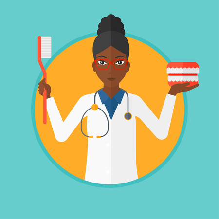 An african-american dentist holding dental jaw model and a toothbrush. Female dentist showing dental jaw model and toothbrush. Vector flat design illustration in the circle isolated on background. Stock fotó - 63813066