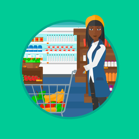 consumer goods: An african-american young woman pushing a supermarket cart with some goods in it. Customer shopping at supermarket with cart. Vector flat design illustration in the circle isolated on background.