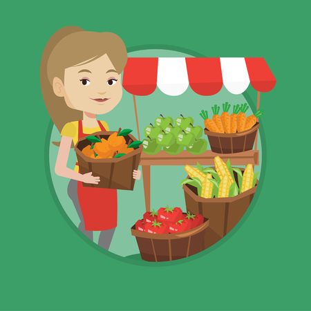 Young greengrocer standing near stall with fruits. Greengrocer standing near market stall. Greengrocer holding basket with fruits. Vector flat design illustration in the circle isolated on background.