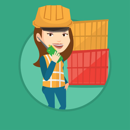 docks: Young port worker talking on wireless radio. Port worker standing on cargo containers background.