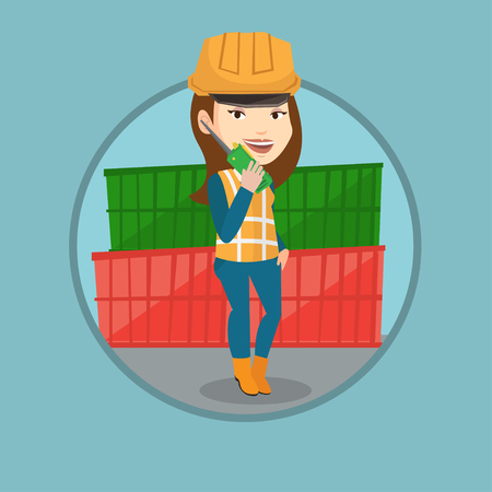 docker: Young port worker talking on wireless radio. Port worker standing on cargo containers background.