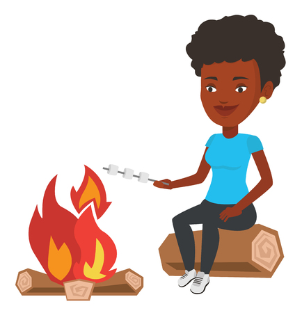Woman roasting marshmallow over campfire.