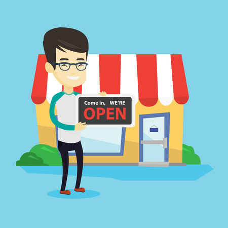 Friendly asian shop owner holding an open signboard. Cheerful smiling shop owner standing in front of small store. Man inviting to come in his shop. Vector flat design illustration. Square layout.