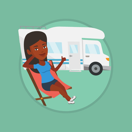 African woman sitting in chair and giving thumb up on the background of camper van. Ilustração