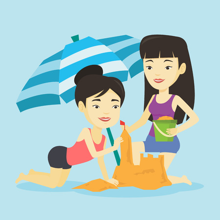 Young asian friends making sand castle on the beach under beach umbrella. Smiling friends building sandcastle.