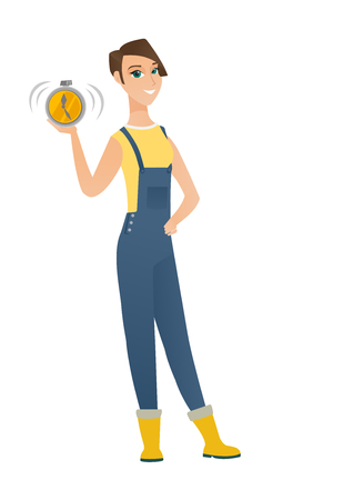 agrarian: Caucasian farmer in coveralls showing ringing alarm clock. Full length of young farmer with alarm clock. Happy farmer holding alarm clock. Vector flat design illustration isolated on white background.