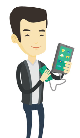 Smiling asian man recharging his smartphone with mobile phone portable battery. Young man holding a mobile phone and battery power bank. Vector flat design illustration isolated on white background. Stock Illustratie