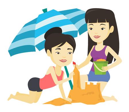 Two friends building sandcastle on beach.