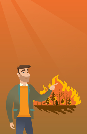 Young caucasian man pointing at forest in fire. Frustrated man standing on the background of a big forest fire. Concept of environmental destruction. Vector flat design illustration. Vertical layout.