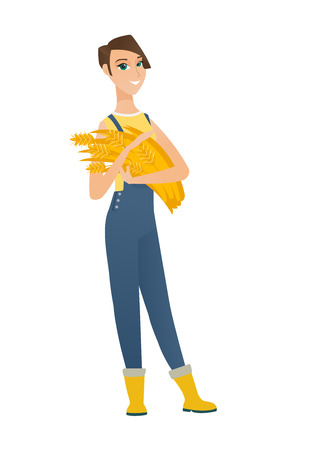 agrarian: Young caucasian female farmer in overalls holding hay in hands. Full length of happy female farmer with hay in hands. Farmer carrying hay. Vector flat design illustration isolated on white background.