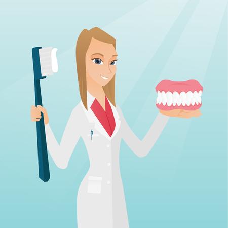 Dentiste avec un modèle de mâchoire dentaire et une brosse à dents. Banque d'images - 79085951