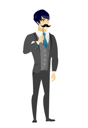 Young asian groom holding a fake paper moustache on a stick in front of his face. Cheerful groom with a fake mustache. Vector flat design illustration isolated on white background.