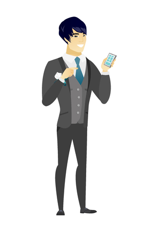 Happy asian groom holding a mobile phone and pointing at it. Full length of young groom with a mobile phone. Groom using a mobile phone. Vector flat design illustration isolated on white background.