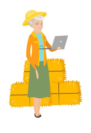 Caucasian farmer using a laptop on the background of hay bales. Full length of senior farmer working on a laptop. Farmer holding a laptop. Vector flat design illustration isolated on white background.