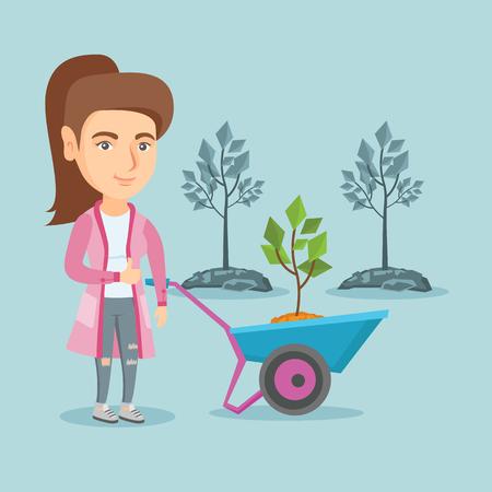 Young gardener pushing wheelbarrow with tree and giving thumb up. 向量圖像