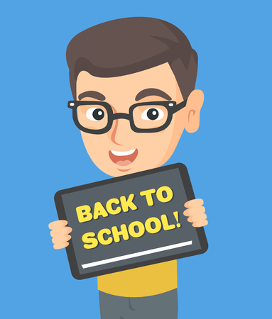 Happy little caucasian schoolboy in glasses holding a tablet computer with text back to school.