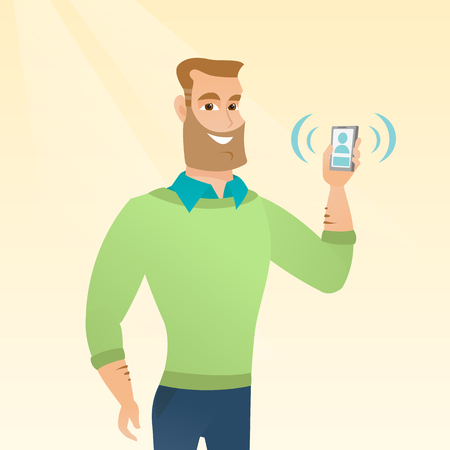 若い白人の笑顔の男は鳴っている携帯電話を保持しています。幸せな男は、電話の呼び出しに応答します。鳴っている電話を手に見せてひげと流行