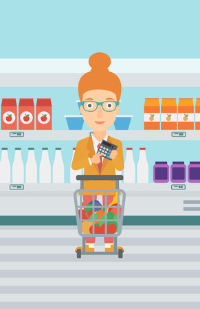 A woman standing near shopping cart and holding a calculator in hands on the background of supermarket shelves with products vector flat design illustration. Vertical layout. Illustration