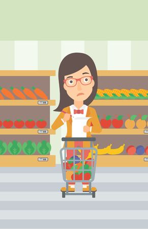 A thoughtful woman standing with full supermarket trolley and holding a shopping list in hands on the background of shelves vector flat design illustration. Vertical layout. Vectores