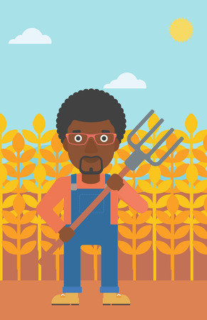 An african-american man standing with a pitchfork on the background of wheat field vector flat design illustration. Vertical layout.