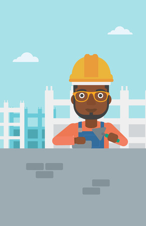 An african-american bricklayer with a spatula and a brick in hands on a background of construction site vector flat design illustration. Vertical layout.