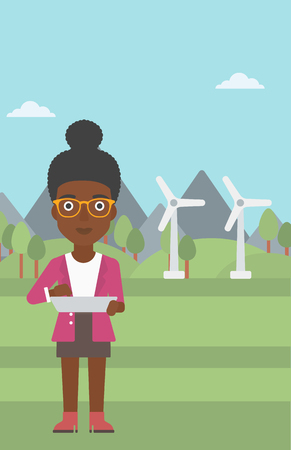 An african-american woman holding a tablet computer in hands on a background with solar pannels and wind turbins vector flat design illustration. Vertical layout. Illusztráció