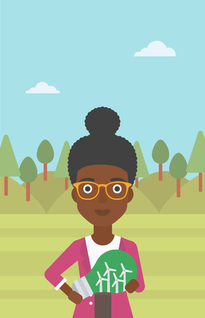 An african-american woman standing on the background of green forest and holding in hands a big light bulb with small wind turbines inside vector flat design illustration. Vertical layout. Vettoriali