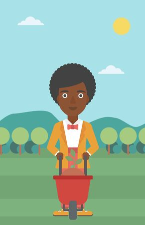An african-american woman standing with a plant and soil in a wheelbarrow on the background of mountain landscape vector flat design illustration. Vertical layout.