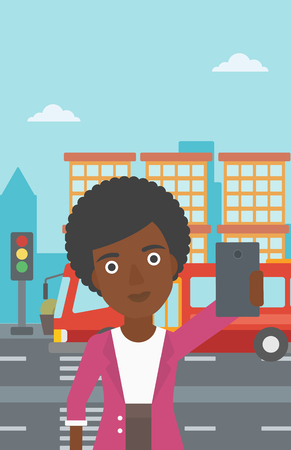 An african-american woman making selfie. Woman taking photo with cellphone. Woman looking at smartphone and taking selfie on the background of city. Vector flat design illustration. Vertical layout.