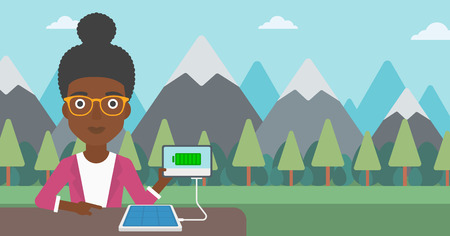 An african-american woman charging tablet computer with solar panel on a background of mountains. Charging digital tablet from portable solar panel. Vector flat design illustration. Horizontal layout. Illustration