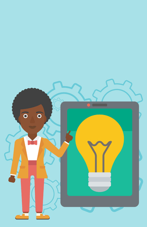 big screen: An african-american woman pointing at a big tablet computer. Woman standing near a big tablet computer with a light bulb on a screen. Vector flat design illustration. Vertical layout.