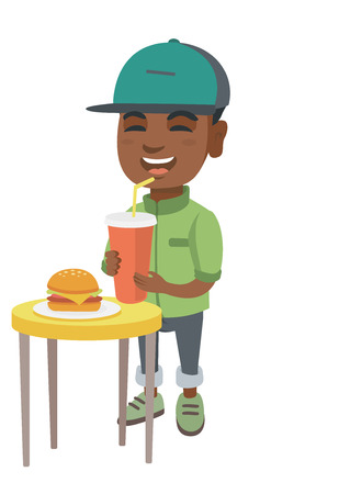 Little african-american laughing boy drinking soda and eating cheeseburger.