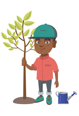 African-american smiling boy planting a tree. Eco-friendly boy standing near newly planted tree and watering can.