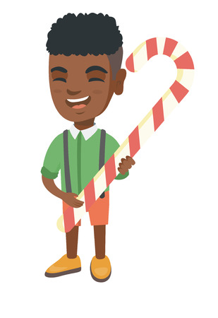 Happy African-American little boy holding a Christmas candy cane. Full length of cheerful boy eating Christmas candy cane.