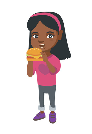 Little african-american girl eating a hamburger with appetite. Cheerful girl holding a big hamburger.
