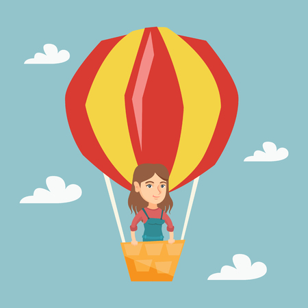 Young Caucasian woman flying in a hot air balloon. Happy woman standing in the basket of hot air balloon.