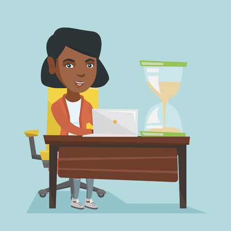 Young african business woman sitting at the table with hourglass symbolizing deadline.
