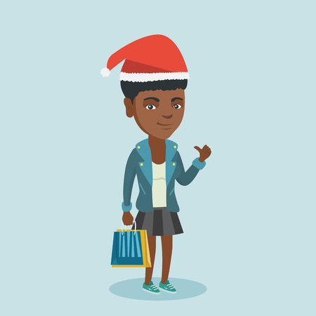Young african-american woman in santa hat holding shopping bags and giving a thumb up.
