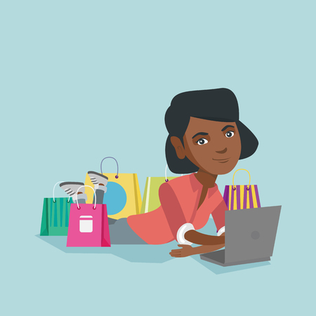 Young african-american woman using a laptop for online shopping. Woman lying with a laptop and shopping bags around her. Woman doing online shopping. Vector cartoon illustration. Square layout. Illustration