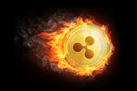 Golden Ripple coin flying in fire flame. Blockchain token grows in price on stock market concept. Burning crypto currency Ripple symbol illustration isolated on black background. Stock Photo