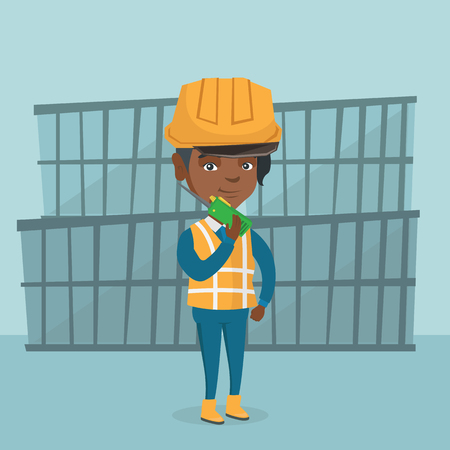 African-american port worker in hard hat talking on wireless radio. Port worker standing on the background of cargo containers and using wireless radio.