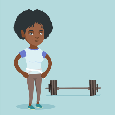 Young african-american woman measuring her waistline with a tape. Happy woman standing next to the barbell and holding a centimeter tape on a waistline.