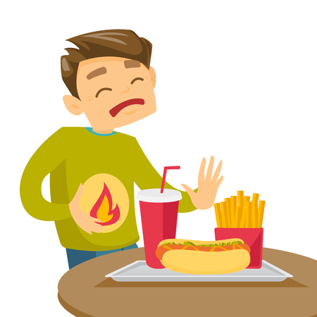 Caucasian man standing near table with fast food and having stomach ache from heartburn.