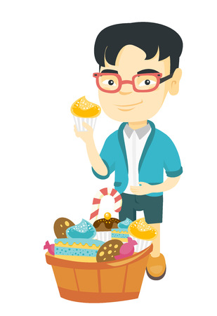 Little asian boy holding a yummy cupcake and stroking his belly. Happy boy standing near the bowl full of sweets. Vector sketch cartoon illustration isolated on white background.